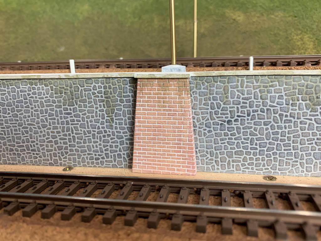 Colonna di mattoni in prossimità del palo della linea aerea